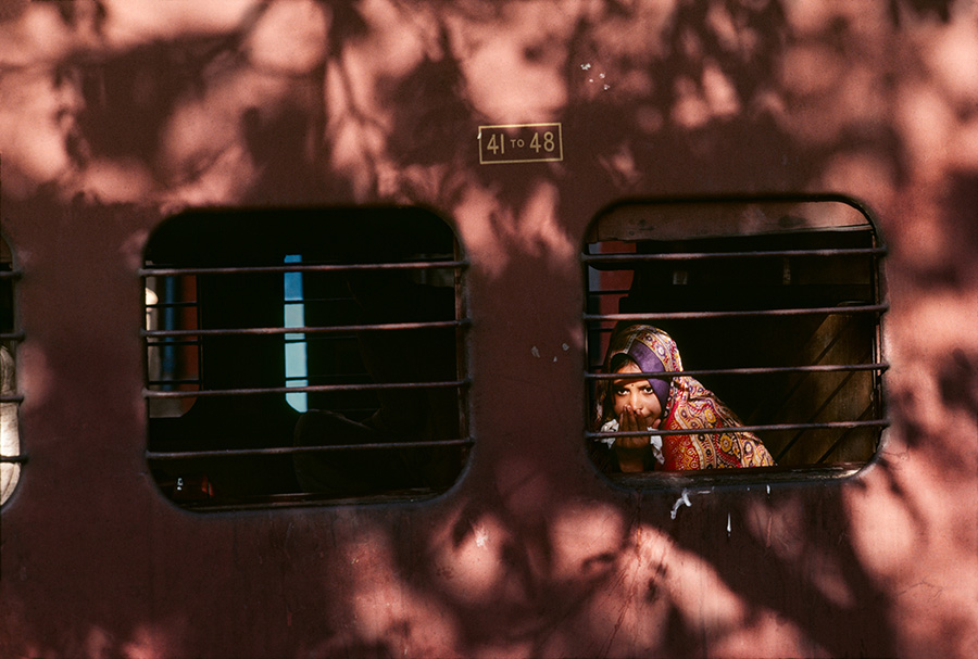 00246_01 An Indian girl peers out of a train window, 1983.
