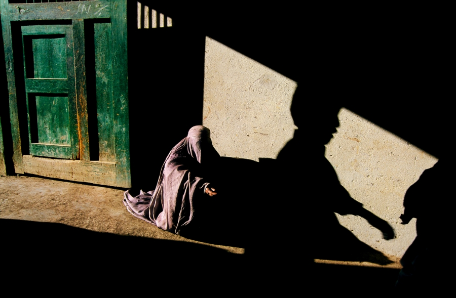 Kabul, Afghanistan, 2002, AFGHN-10156. Beggar and shadow. On this particular day in Kabul, McCurry found a beggar women seeking charity outside a mosque. The ominous shadows of the buildings and passers-by convey a sense of intense isolation. It is a scene that has a changed little over the years. 'Every time I've returned,' McCurry recalls, 'I have found the same woman, begging by the same door.'