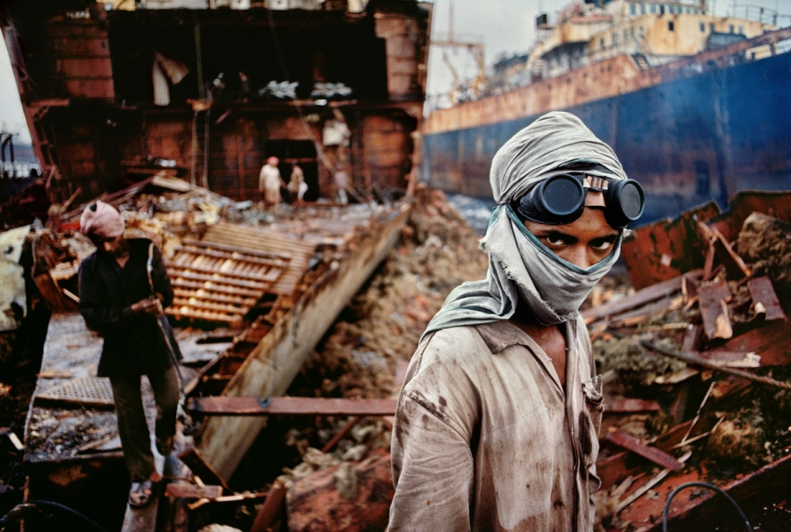 Bombay/Mumbai, India, 1994, INDIA-10207. Welder in a ship-breaking yard. Vessels from around the world end up in this Bombay/Mumbai ship-breaking yard to be broken down into scrap. This worker is one of the many that reduce these colossal ships to tons of valuable iron. It is a dirty and dangerous job. Before turning to his next task, this worker's eyes catch McCurry's camera. Magnum Photos, NYC5952, MCS1993006 K030. From the tangle of deconstruction in the shipbreaking yard of Bombay, a young welder stepped forward in 1994 to engage the camera. His eyes, redoubled by the goggles on his forehead, draws our gaze away from the ship's empty hold and we wonder about this young man, whose face we cannot read fully, whose head is protected only by the cloth that covers his mouth. The promise of our gaze meeting, through a photograph, the look of another across time, and vastly different spaces is one of the signature strengths of McCurry's art. Bannon, Anthony. (2005). Steve McCurry. New York: Phaidon Press Inc., 27. National Geographic Magazine. Vol. 188, No. 3, pgs.56-57, March 1995, Bombay: India's Capital of Hope. Phaidon, 55, Portraits, South Southeast, Iconic Images, final book_iconic, iconic photographs Goggles and scarf shield this worker from the choking dust and smoke of the ship breaking yard. Old ships are brought from all over the world to be cut up for scrap metal. National Geographic: John McCarry (March 1995) Bombay: India's Capital of Hope, National Geographic. (vol.187 (3)) pp.42-67 Portraits_Book South Southeast_Book Steve Mccurry_Book Iconic_Book PORTRAITS_book Untold_book PORTRAITS_APP final print_MACRO final print_Sao Paulo final print_Birmingham India_Book retouched_Sonny Fabbri 02/26/2015