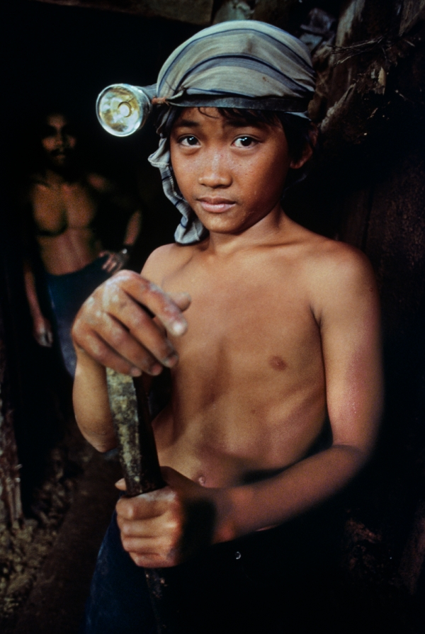 An 11-year-old boy stands outside a gold mine where he works in Mindanao, Philippines, 1985. Portraits_Book PORTRAITS_Book