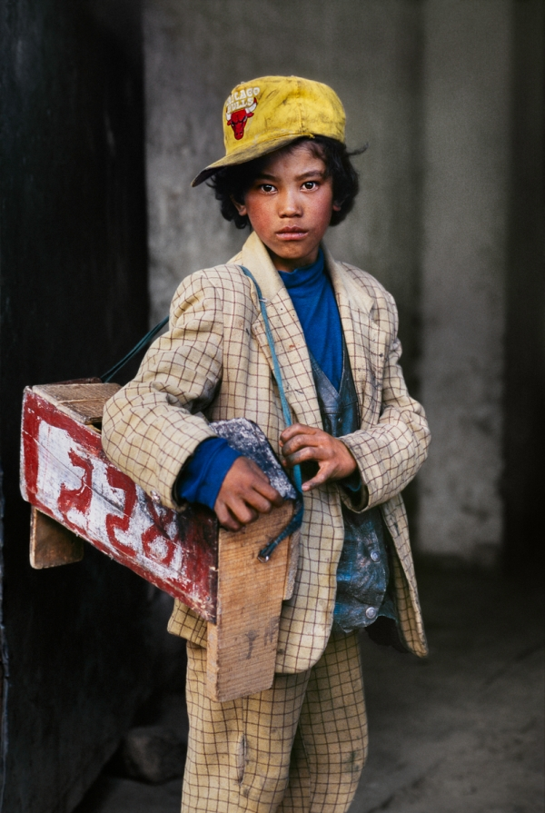 Shoeshine boy, Lhasa, Tibet, 2000 This shoeshine boy is accustomed to catching the eye of a potential customer. Working on the street, he pauses for a moment to see if McCurry wants more than just a photograph. The numbered stool indicates that he is part of a bigger operation of vendors traversing the city in search of business. Phaidon, Iconic Images, final book_iconic final print_Birmingham retouched_Sonny Fabbri 06/18/2013