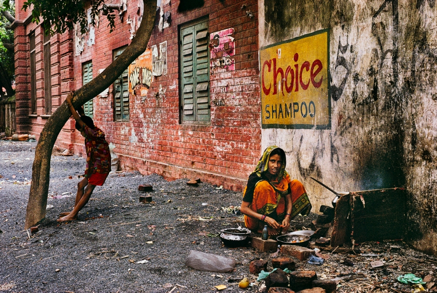01896_11, 508665, India 50 Years After, Calcutta, India, 10/1996, INDIA-10379. An Indian woman prepares a meal under a shampoo advertisement. India_Book retouched_Sonny Fabbri 02/03/2015