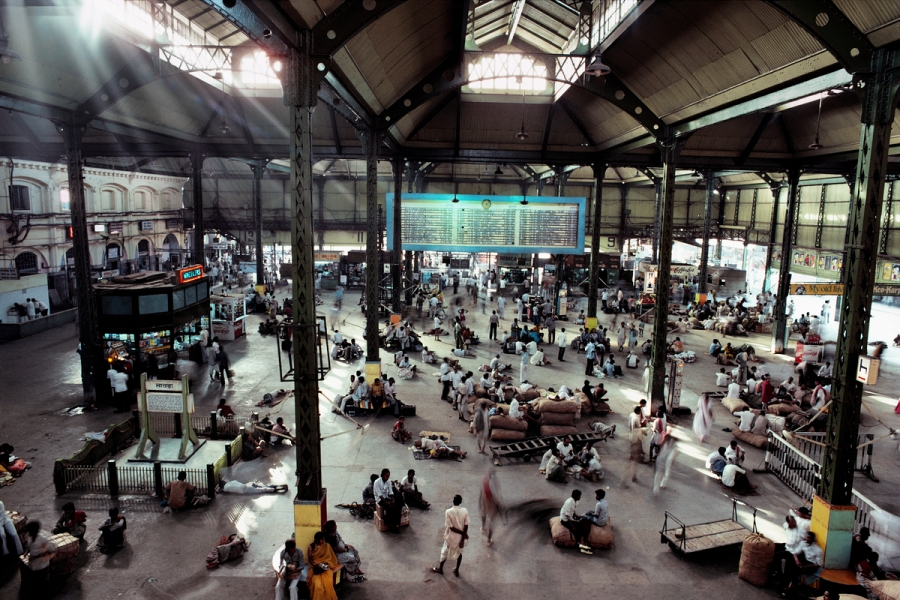 Howrah Station, Calcutta, India, 1983 As the midday sun streams through the skylights, passengers wait for their trains. Like a movie frozen in time, one can almost hear the noise of people talking, walking, coughing and laughing, and the clatter and screech of the trains as they arrive and depart, the sounds echoing beneath the high ceilings. Howrah Station, Calcutta, India, 1983. Pg. 27, Untold: The Stories Behind the Photographs Phaidon, Iconic Images, final book_iconic The Imperial Way_Book Untold_book The Great Railway Bazaar_Book
