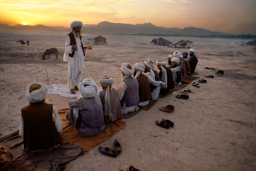Prayers, Peshawar, Pakistan, 1984 In a scene that has changed little in hundreds of years, these men are facing west towards Mecca, performing the sunset prayer: Salt Al-Maghrib. As dusk falls over the region, the red glow spreads out from the mountains as the men's teacher delivers a lesson, 11/1984 Phaidon, Iconic Images, final book_iconic, page 64. Iconic_Book