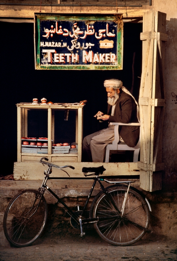 """00178_05; 00136_02; Kandahar; Qandahar; Afghanistan; 1998; AFGHN-10002. Teeth-maker. With no public health service, Afghani teeth-makers can often be found plying their trade on street corners or in makeshift shops like this one in Kandahar. In the combination of the raised platform, the sign hanging from above and the blackened 'backdrop', McCurry captures a scene of surreal theatricality. """"An Afghan dentist crafts a set of dentures in the old quarter of Qandahar. Few Afghans will visit a dentist in their lifetime. I had walked past this shop many days, and happened to meet him as he arrived at his shop at five thirty in the morning on his bicycle.""""- George Eastman House. Magnum Photos, NYC14801, MCS1998016 K001 Phaidon, In the Shadow of Mountains, Iconic Images, final book_iconic, iconic photographs With no public health service in Afghanistan, teeth-makers can often be found plying their trade on street corners or in makeshift shops like this one in Kandahar. In the combination of the raised platform, the sign hanging from above the blackened 'backdrop' McCurry captures a scene of surreal theatricality. In the Shadow of Mountains_Book Iconic_Book final print_Birmingham retouched_Sonny Fabbri 6/3/2015"""