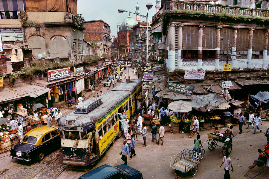 "Tram, Calcutta, India, 1996; A Tram, Calcutta, India, 1996 MCS1996002 K010 Magnum Photos, NYC5923 ""For McCurry, Calcutta is the most visual city on the planet, spinning with chaos and clutter, crumbling under the weight of its overpopulation, utterly out of control, yet vital and alive. Vendors spill into streets, which hold a confusion of cars, trams, rickshaws, bicycles and pedestrians. So how to make this picture? McCurry looked for an office or apartment on a second floor of a street corner. 'And that is the wonder of the place. Twenty minutes later, I am on a bed in a couple's apartment, making the picture and staying on for a cup of tea."" Anthony Bannon. (2005). Steve McCurry. New York: Phaidon Press Inc., 37. National Geographic, March 1997, India: Fifty Years of Independence Phaidon, 55, South Southeast, Iconic Images, final book_iconic, iconic photographs final print_HERMITAGE Dirty, hot, smoggy, friendly- that's how one resident describes Calcutta, a city so humid even the buildings seem to sweat. With crowded streets pockmarked with potholes, an unreliable phone system, and a long love affair with Marxism, Calcutta is only now trying to lure foreign investors. National Geographic, Jeffrey C. Ward (May 1997). India: Fifty years of Independence. National Geographic, vol. 191(5) A tram winds its way through the streets of Calcutta. Dirty, hot, smoggy, friendly, it is a place so humid that even the buildings seem to sweat. This Calcutta street is a cacophony of visual noise. McCurry spent a long time searching for a way to capture the energy and vitality of this most unique of cities. His response was to find a vantage point above street level. Fortunately, he was welcomed into an apartment on the street corner by a young couple. After taking this image he stayed for a cup of tea. South Southeast_Book Steve Mccurry_Book Iconic_Book final print_Sao Paulo final print_Birmingham final print_HERMITAGE retoucher_Sonny Fabbri 3/24/2015"