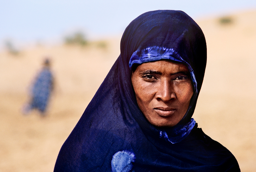 00365_12, Gao, Mali, 1986, MALI-10006. Tuareg woman. The Tuareg are a semi-nomadic tribe who live within the Sahara desert. For much of the year they move with their herd, but they often inhabit regions for fixed periods when they grow crops. Traditionally, the tribe is very insular, and one can detect wariness in the way this woman returns McCurry's gaze. Magnum Photos, MCS1987002 K500 final print_Milan book_The Unguarded Moment book_Iconic Photograhs book_PORTRAITS final print_Genoa final print_Perugia retouched_Sonny Fabbri 03/14/13
